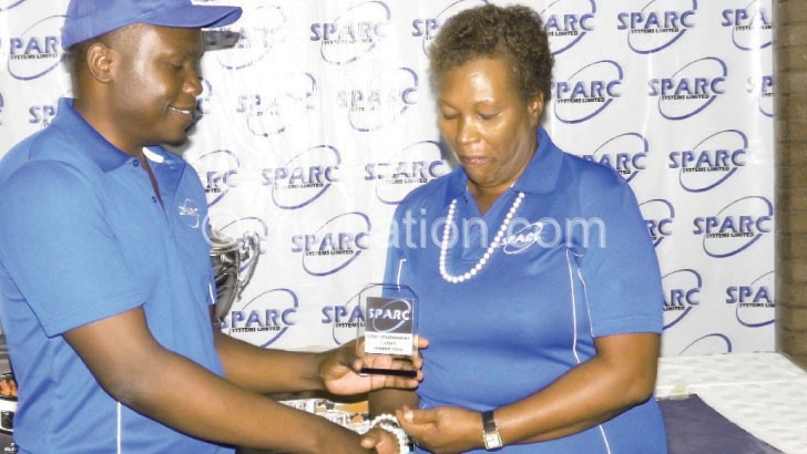 Nkwanda (R) receives her prize from Phiri