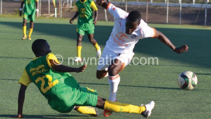 Wanderers' Peter Wadabwa (R) is stopped by a Dwangwa defender in their first-round encounter