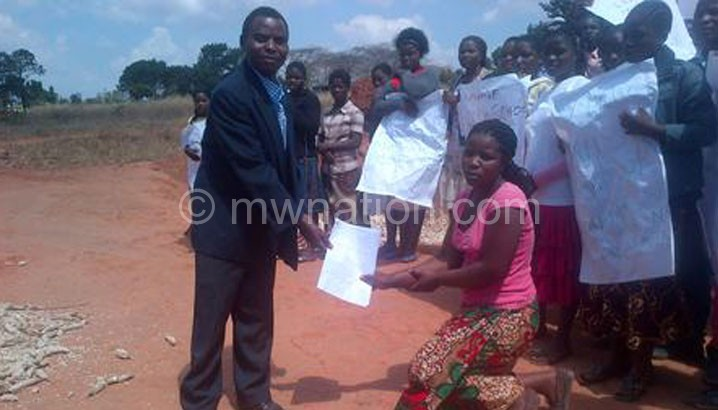 T/A Khosolo (R) receiving the petition from one of the girls