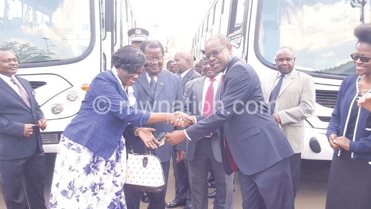 Tembenu (2nd R) hands over the Cashgate buses to beneficiaries