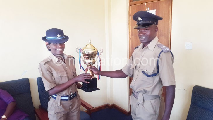 Nhlane (R) and a colleague, showing a trophy