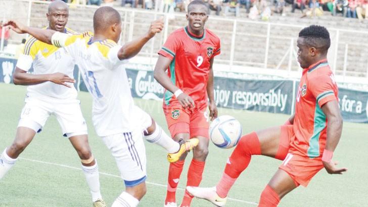 Flames' Gabadinho Mhango (R) tries to beat  a Swaziland player