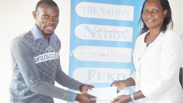 Kachali (R) hands over a cheque to Mwale