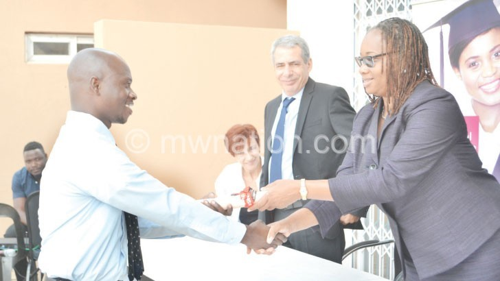 Samala (L) receiving the award from Banda as other officials look on