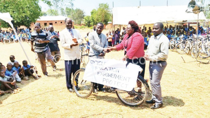Pwele (2nd R) hands over a bicycle to Mdooko