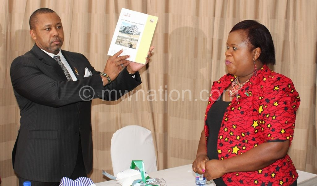 Chilima shows off the report as NCIC chief executive officer Linda Phiri looks on
