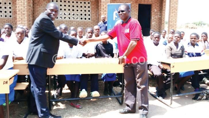 Kadango (R) shaking hands with Mkonda after handing  over the desks