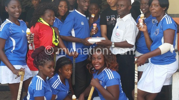 Chipeta (in white shirt) makes a symbolic meal presentation to Genetrix players