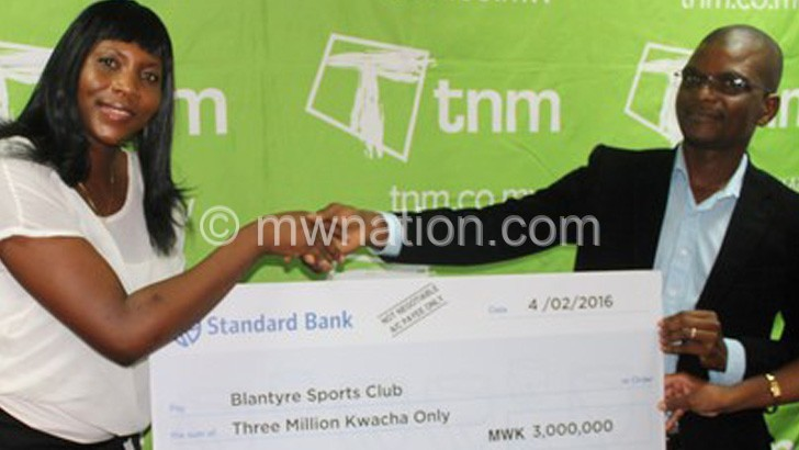 Makata (R) presenting a symbolic cheque to Karuku during  the ladies golf sponsorship launch