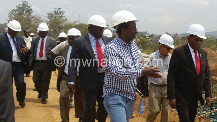 Mwanamvekha (R) tours the construction site