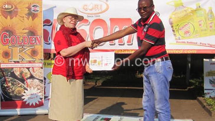 Mwanja (R) hands over the bottles  to Machinjiri
