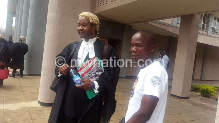 Mambulasa (L) exchanging notes with Gwanda outside the court