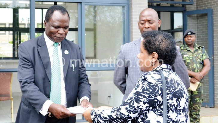 Juma (R) presenting the petition to Chakwera as other officials look on