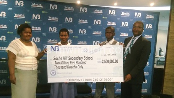 Phiri (L) makes a symbolic cheque presentation to Chalamanda as other officials look on