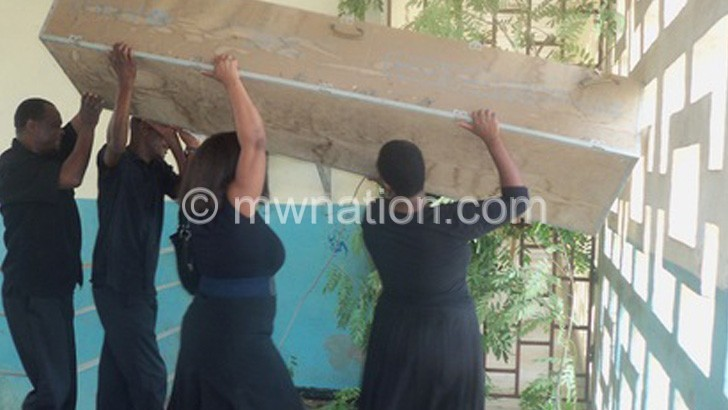 Some of the employees carrying a mock coffin and dressed in  black during the stand-off