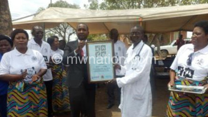 Chipungu (in suit) holding a  certificate with Gondwe
