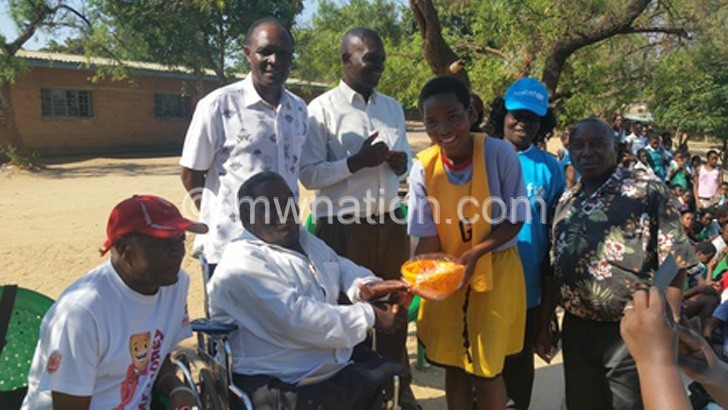 Chiutsi presents a ball to Blantyre Girls netball captain Wezzie Msiska as Saenda (L) and other officials look on