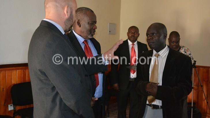 Mustard (L) talks to Journalism Department head Ellard Manjawira (R) as Saka (2ndL) and other officials listen