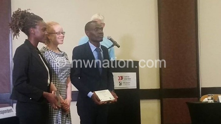 Masanjala (L) and Mchizi (R) pose with a UN represantitive on persons with albinism
