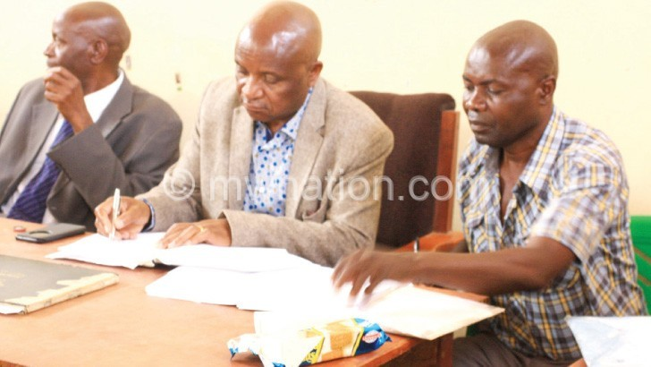 Mkandawire (C) sign the contract