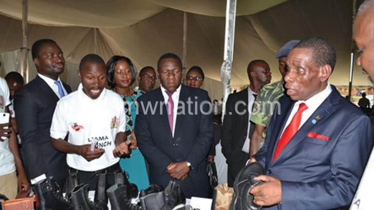 Mwanamvekha (R) appreciates leather products prior to Liama launch