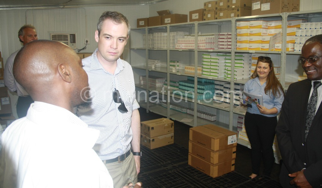 Wharton (2nd L) listens to a health official as Chief of Health Services Dr Charles Mwansambo (R) smiles