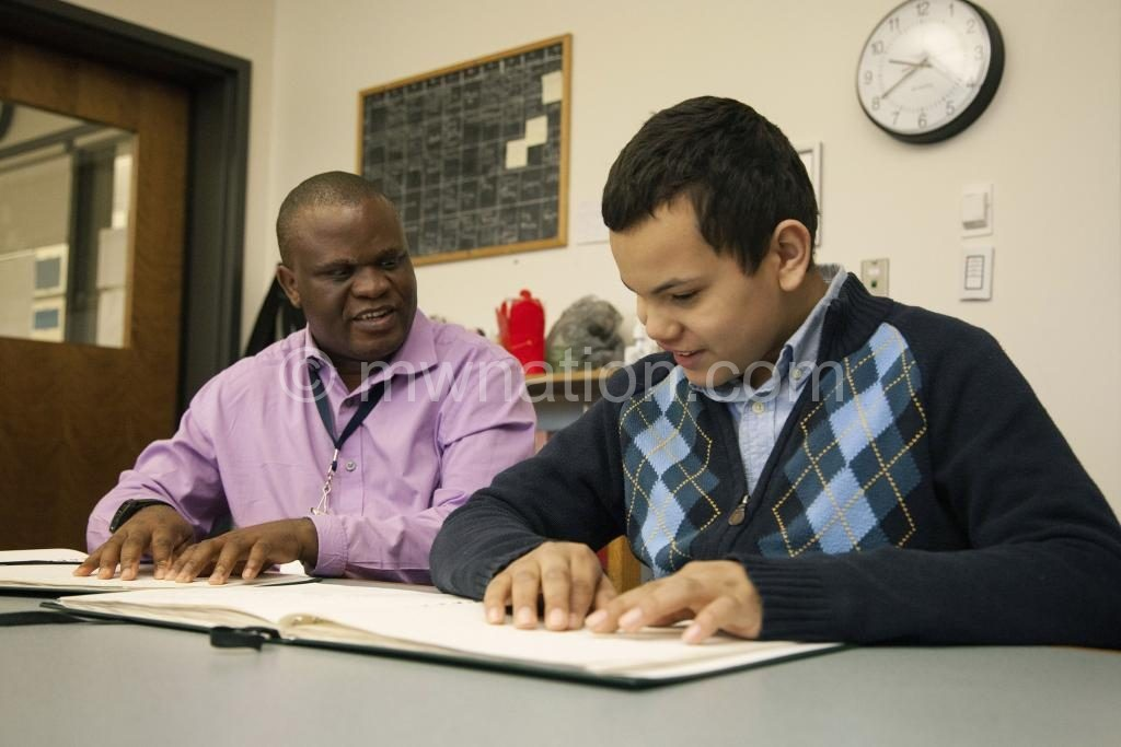 A teacher helps a  visually impaired child in class