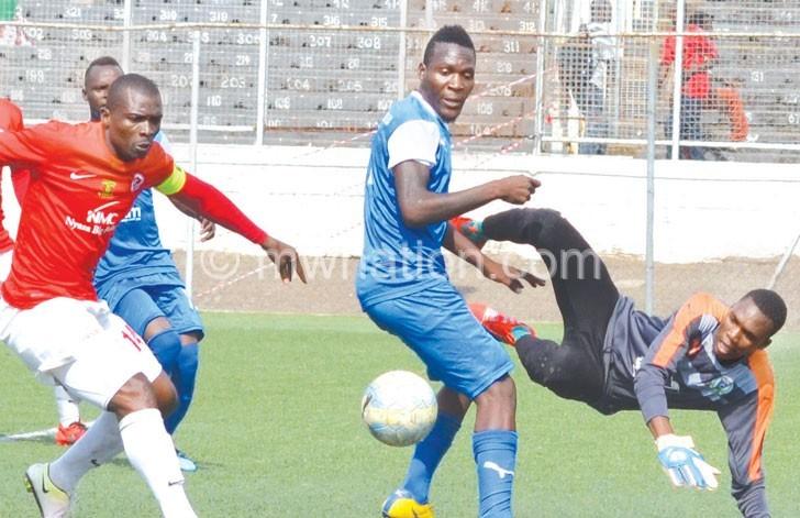 Karonga United goalkeeper Lloyd Munthali (R) makes a save to deny Bullets