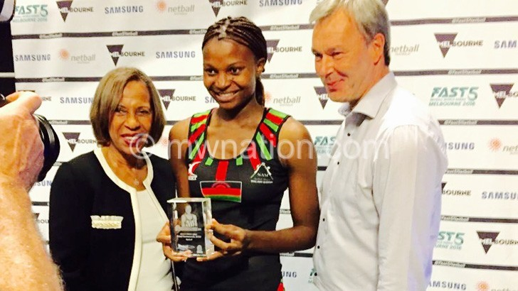 Mwawi (C) flanked by officials, shows off her IWGA award