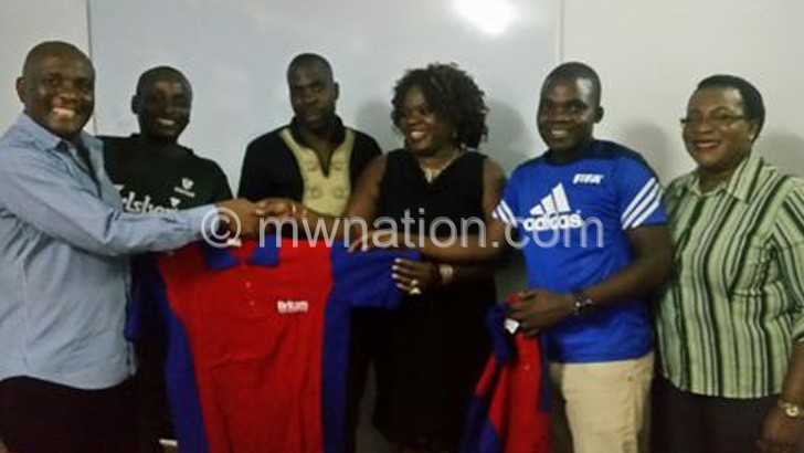 Missi (L) receives a golf shirt from Nkhoma as organising committee  members look on
