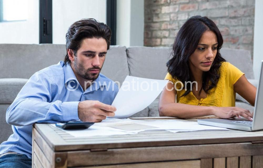couple in living room paying bills | The Nation Online