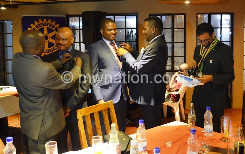 Welcome home dears. Past presidents decorates the new rotarians at the inductio dinner in Lilongwe. Looking on is incumbent club president Vjay Mittal. Photo by Fatsani Gunya 1 | The Nation Online