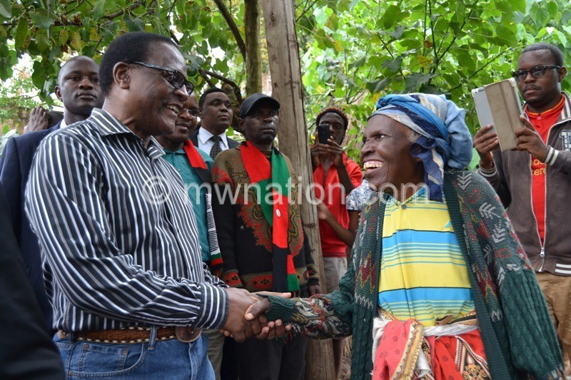 Chakwera cheers an old woman at Kaliyeka whose house was entirely demolished in the Saturday night floods. Photo by Fatsani Gunya | The Nation Online