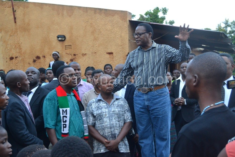 Chakwera hails one of the local heroes in the disaster at Kawale 1 in Lilongwe on Sunday. He also asked the community to be each others brothers keeper. Photo by Fatsani Gunya | The Nation Online