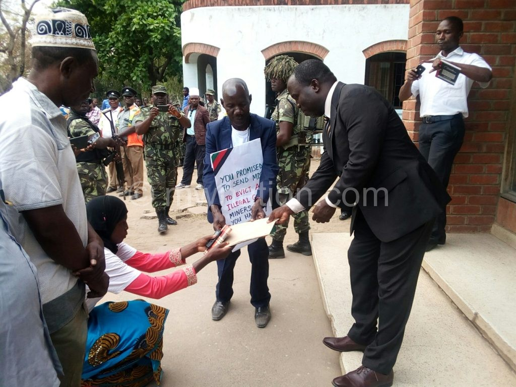 Chimphepo in black suit receiving the petition from one of the community members   The Nation Online