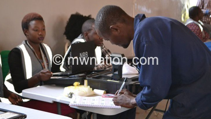 A VOTER SIGNING FOR HIS STICKER | The Nation Online