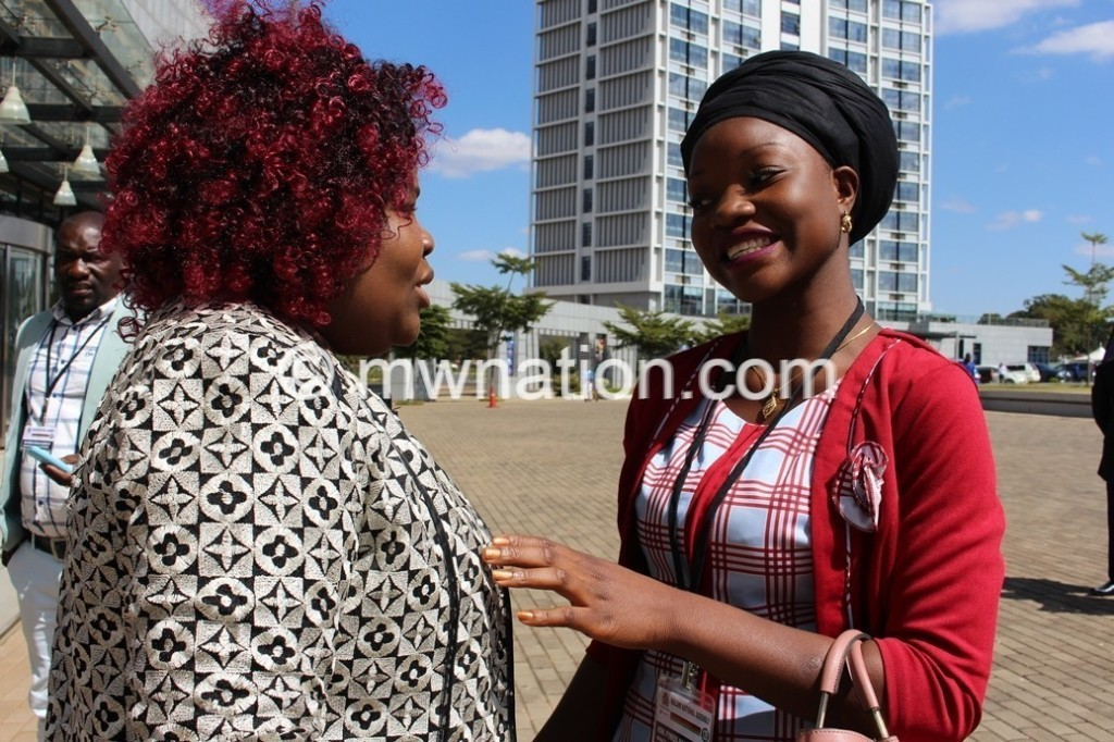 Malawis youngest MP Fyness Mangojiwa in red interacts with fellow lady newcomer.C Govati Nyirenda 2 | The Nation Online
