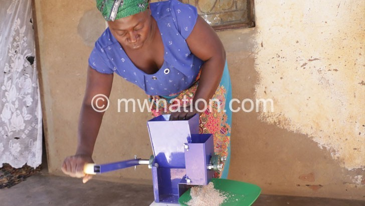 Moyo demonstrates how she grinds groundnuts mannually | The Nation Online