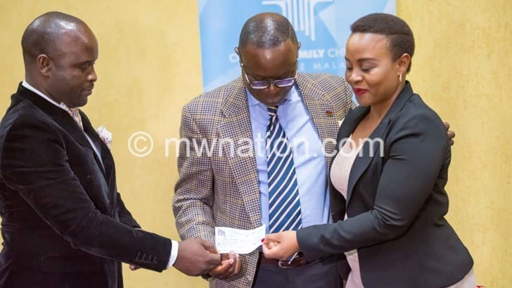 Rusell Golden giving a cheque to pastor Mwamadi | The Nation Online