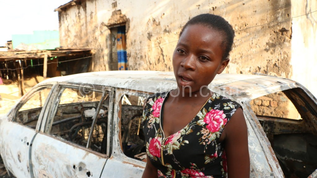Tamara Isaac in front of a car that was burned by the police | The Nation Online