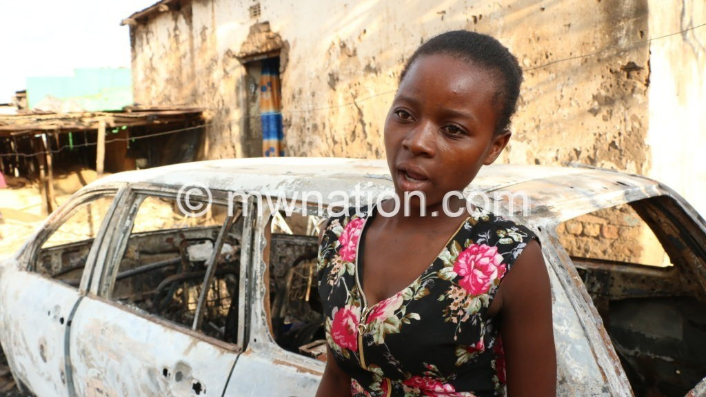 Tamara Isaac in front of a car that was burned by the police 1024x576 1 | The Nation Online